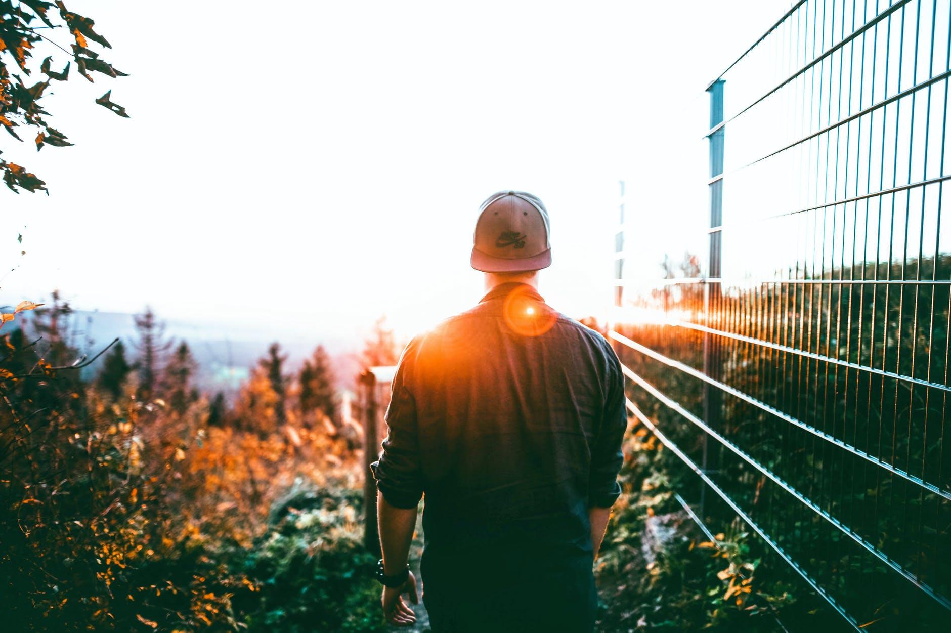 man walking toward sun.jpeg